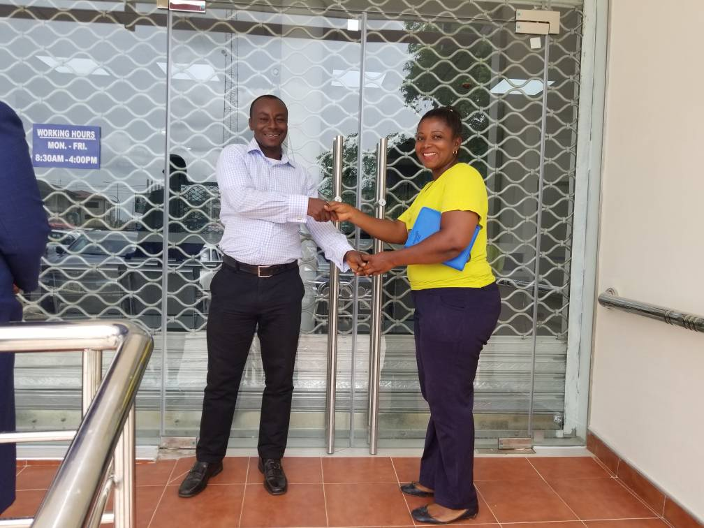 THE CONSULTANT MAD. ROSEMARY DWAMEN HANDING OVER THE OFFICE KEYS TO THE ESTATE MANAGER MR FREDERICK OPPONG