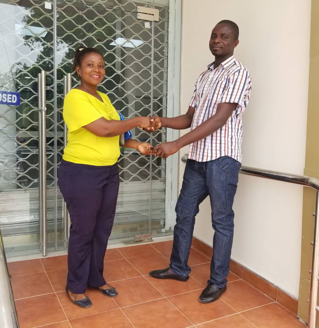 THE FOREMAN MR KOJO ANTWI HANDING OVER THE OFFICE KEYS TO THE CONSULTANT MAD. ROSEMARY DWAMEN
